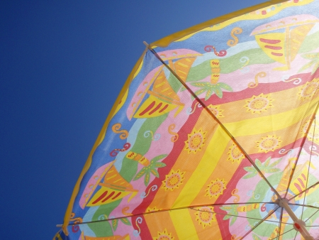 Colourful parasol and clear blue sky in background
