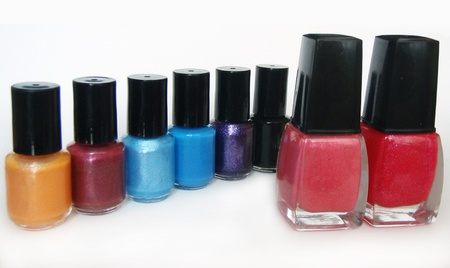 Colourful nail polishes in a line and two bigger ones