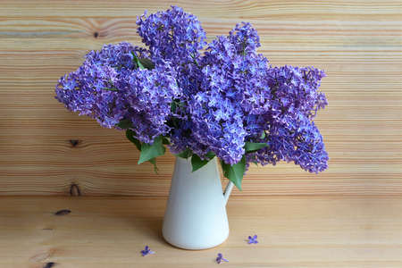 Beautiful lilac flowers in vase on wooden background