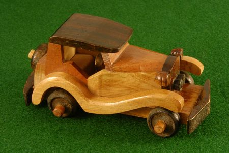 A hand carved wooden toy car.