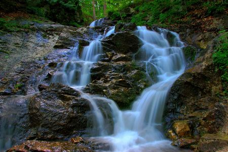 the  then: A waterfall is split and then rejoins as it passes over the rocks. Stock Photo