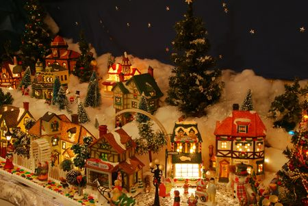 A miniature Christmas village is lit up.  The little people are all about involved in a variety of holiday activities.   Stock Photo