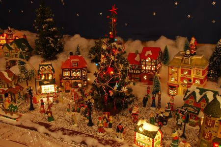 christmas carols: Little people fill the town center of this miniature village.  Even have a few Santa Clauses. Stock Photo