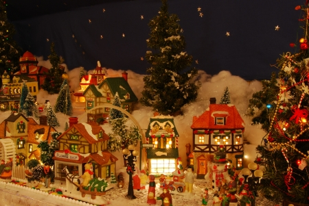 A miniature Christmas village is all lit up.  The little people are all about involved in a variety of holiday activities. Stock Photo