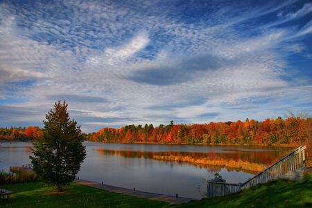 cirrus: The afternoon sun lights up the fall colours on the rivers shore.  Stairs lead down to the dock in the foreground. Stock Photo