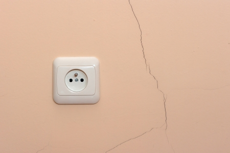 A crack in the wall next to an electrical outlet photo