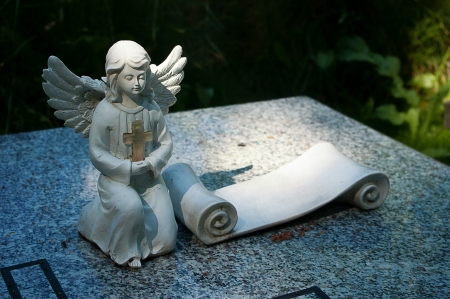 Angel on the grave with the inscription card. photo