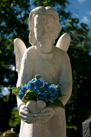 angel cemetery: Cemetery angel with blue flowers.