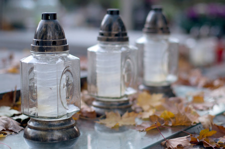 Autumn cemetery, candles and fallen leaves.