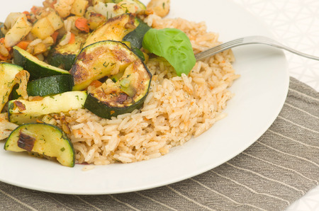 Vegan meal consisting of risotto with vegetables served on a plate.