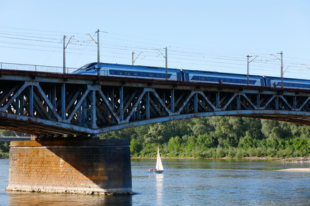 The Vistula River in Warsaw, over which the bridge stands. A train travels along the bridge, and a small sailing boat flows on the river. Standard-Bild - 101682131