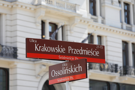 A sign with the street in Warsaw indicating the direction to Ossolinski and Krakowskie Przedmiescie streets. Standard-Bild - 102816308