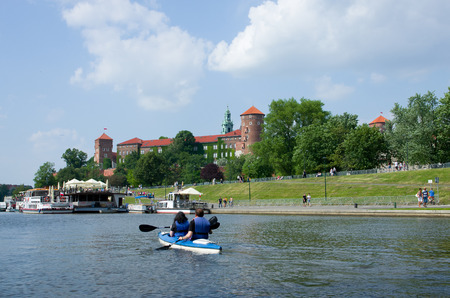 Wawel Castle in Krakow. View from the side of the Vistula River. In the foreground canoeists floating on the Vistula. Standard-Bild - 115217731