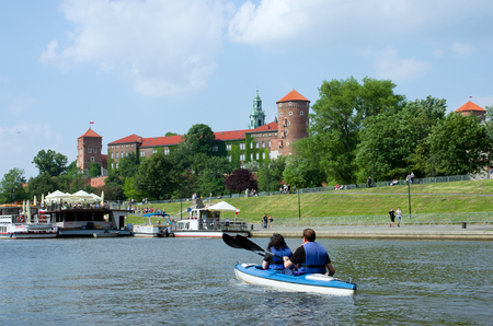 Wawel Castle in Krakow. View from the side of the Vistula River. In the foreground canoeists floating on the Vistula. Standard-Bild - 115217732