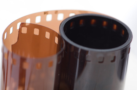 A roll of photographic film of 135 mm on a white background. Standard-Bild - 115239071