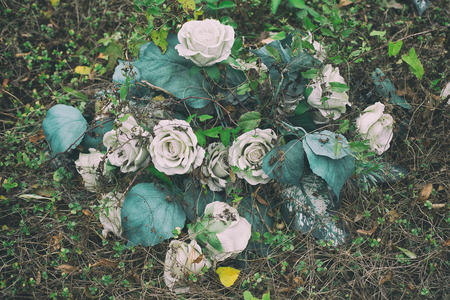 A bouquet of artificial roses on an abandoned grave overgrown with weeds. Stock Photo