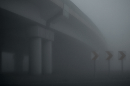 Early morning, dawn. Street and bridge. Foggy morning. Road signs warning about the bend.