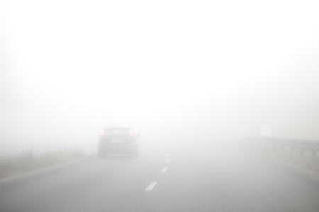 Early morning and thick fog on the road. Cars are driving slowly. Short visibility. Stok Fotoğraf