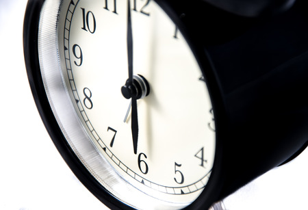 Vintage black clock close-up on a white illuminated background at six o