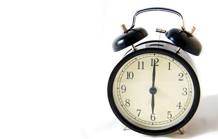 Vintage black clock on a white illuminated background at six o