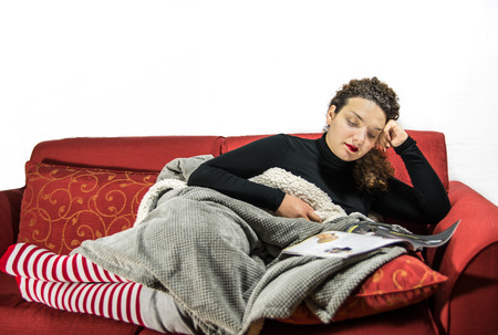 view of an elegant red couch: Beautiful girl relaxing on the sofà with christmas socks