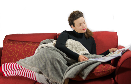 view of an elegant red couch: Beautiful girl relaxing on the sof� with christmas socks