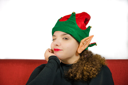 waiting glance: Beautiful girl portrait with green and red christmas elf hat and ear