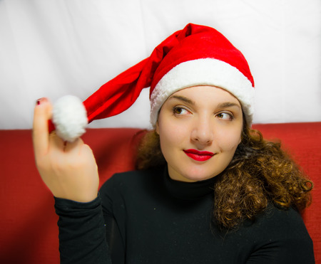 waiting glance: Beautiful girl portrait with Santa Claus hat while dreaming Christmas