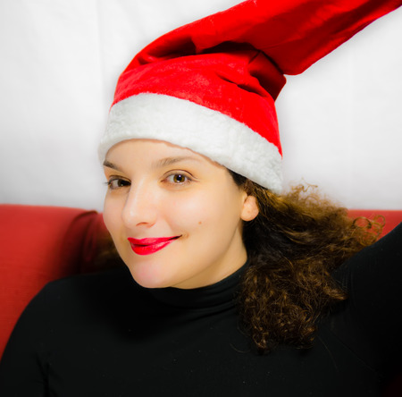 waiting glance: Beautiful girl portrait with Santa Claus hat while smiles