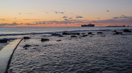 merchant: Merchant ship is leaving Leghorn harbour at sunset