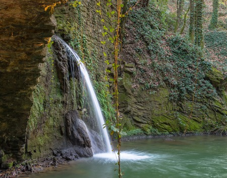 mill valley: Artificial waterfall passes through the ruins of a water mill in Tuscany
