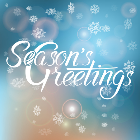 Season's Greetings handwritten text on blurred background with snowflakes.Calligraphic Xmas and New Year holidays design.