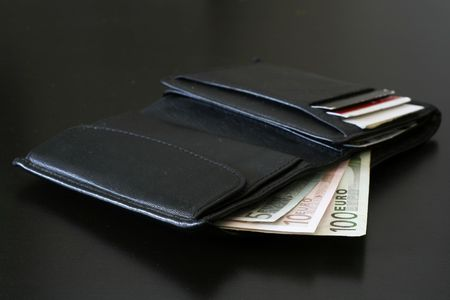 Euro bills coming out of a black wallet. photo
