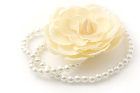 Macro shot of a beautiful flower and pearl necklace isolated on white. Stock Photo