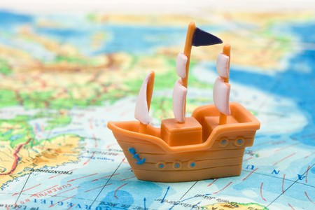 Toy ship on a world map. Travelling by ship concept.