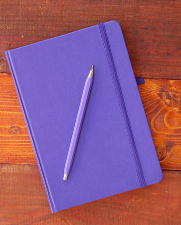 Closed blue notebook and pencil on wooden background