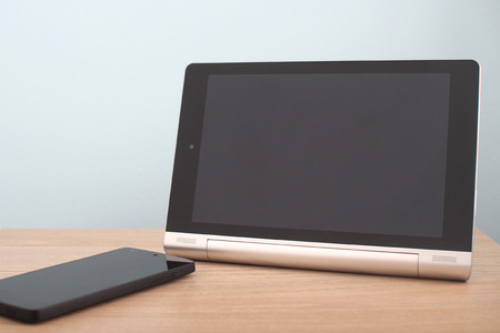 Blank tablet and phone on desk