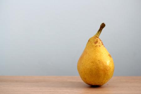 Ripe pear on desk background