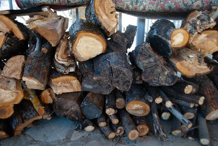 Pile of chopped firewood logs. Stack of wood pieces. Pine timber. Woodpile. Storage of firewood. Dry chopped logs. Firewood wall.