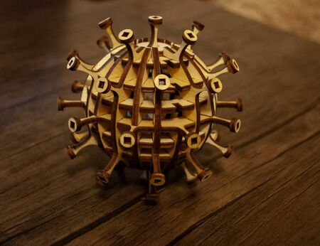 The image of a coronavirus particle made of wood. Woodcraft coronavirus. Wooden virus. Woodcraft art. Covid-19 Banque d'images