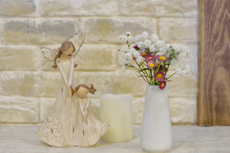wooden statuette of mother and daughter, white candle, vase with wildflowers Stock Photo