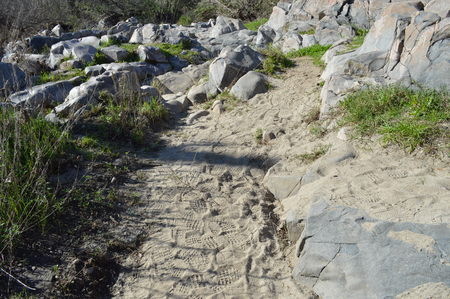 A trail of footprints through rocky terrain. Stock Photo