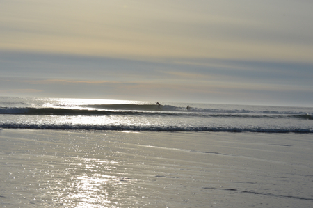 Two distant surfers at sunset.