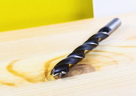 bit: Drill bit close up on wooden plank