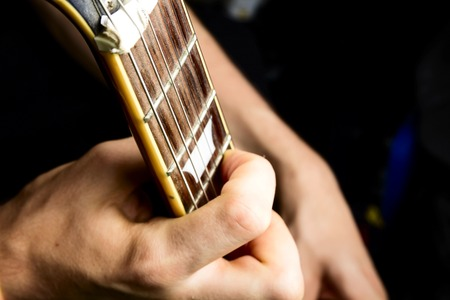 fingering: Sun burst electric guitar played by man