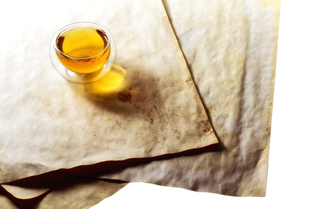 double glass: Double glass tea cup filled with green tea on vintage aged paper