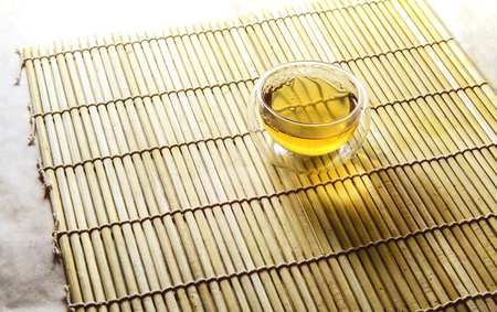 double glass: Double glass tea cup filled with green tea on bamboo mat Stock Photo