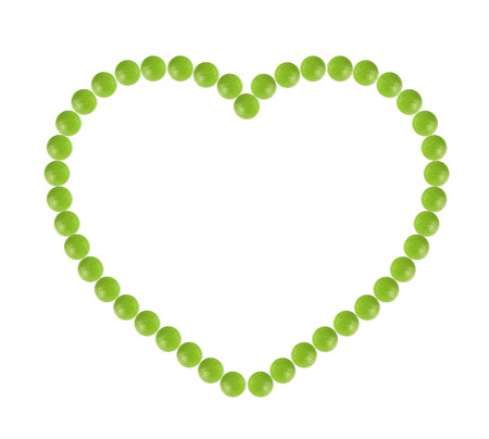 Plenty of green pills shaped in heart form on white background Stock Photo