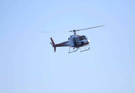 on the skids: News helicopter in flight with a cameraman shooting