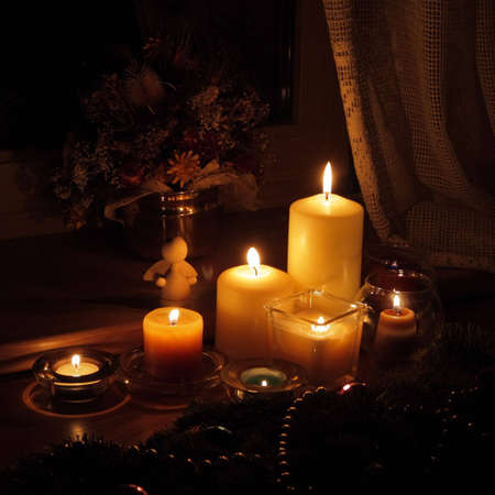 celeb: Candles with Christmas decorations in dark interior